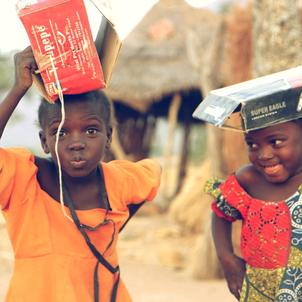 crianças negras com caixas de papel na cabeça